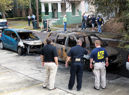 Investigators surround one of the cars that burned across the street from the house. (Robert Morris, UptownMessenger.com)