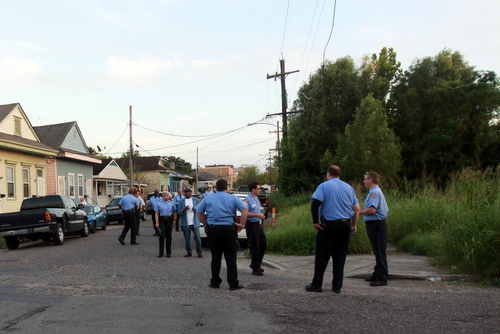 New Orleans Police officers gather around the vacant lot at Foucher and South Saratoga for an anti-crime march in late September, when the property was still covered in tall weeds. (UptownMessenger.com file photo by Robert Morris)