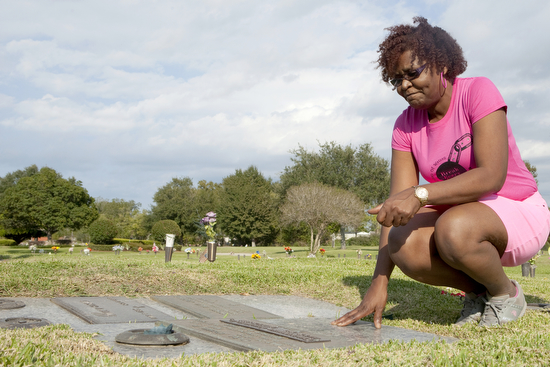 Linn James says a prayer to her son Christopher Guilbeau Jr. and tells him she loves him while visiting his grave in Avondale on Oct. 28, 2013. (Sabree Hill, UptownMessenger.com)