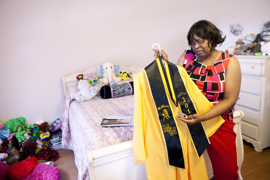 Margaret Washington sits in her daughter Marguerite LaJoy Washington's room, holding LaJoy's McMain graduation gown and medal for Physics. LaJoy was shot and killed while visiting her new boyfriend's home just months after graduating from high school. (UptownMessenger.com file photo by Sabree Hill.)
