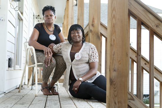 "Cathy Rickmon (left) and Martha Bullock (right) sit on the porch where their sons Orlando ""Lanny"" Rickmon and Desmond O'Neal Bell were murdered on April 23, 2013. ""Losing a child is like losing half a heart,"" said Rickmon. (Sabree Hill, UptownMessenger.com)"