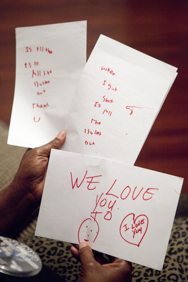 Cathy Rickmon holds notes that Lanny wrote in ICU unable to talk after being shot 13 times in February of 2013. One note asks if all the 13 bullets are out, another says I love you. (Sabree Hill, UptownMessenger.com)