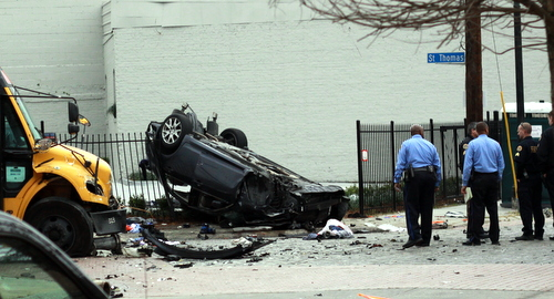 Police examine a car that crashed into a school bus and landed on a fence on St. Thomas Street at Felicity. (Robert Morris, UptownMessenger.com)