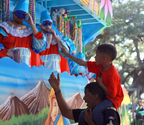 A spectator catches beads during the Krewe of King Arthur parade. (Robert Morris, UptownMessenger.com)