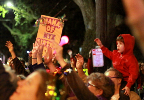 Spectators held up large signs and small children to attract throws from Nyx. (Robert Morris, UptownMessenger.com)