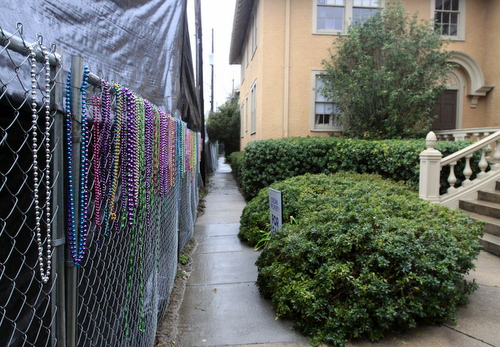 Mardi Gras beads hang on the chain-link fence in front of the tall black tarp, an effort to bring some life back to the otherwise bleak view. (Robert Morris, UptownMessenger.com)