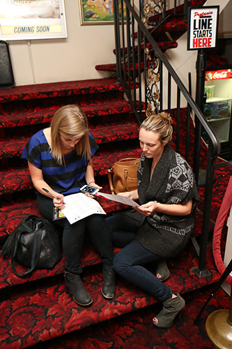 Kate Archer, left, and Whitney Hines, right, fill out their Oscar predictions before Sunday night's award show. (Zach Brien, UptownMessenger.com)