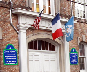 The French flag flies between the American and Louisiana flags outside the front door of Ecole Bilingue. (UptownMessenger.com file photo by Robert Morris)