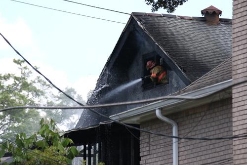 A firefighter battles the blaze at 5940 Freret Street. (Zach Brien for UptownMessenger.com)