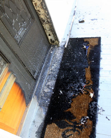 The front door of a home in the 2300 block of Octavia Street remains charred on Tuesday afternoon, with tatters of the American flag that was also burned. (Robert Morris, UptownMessenger.com)