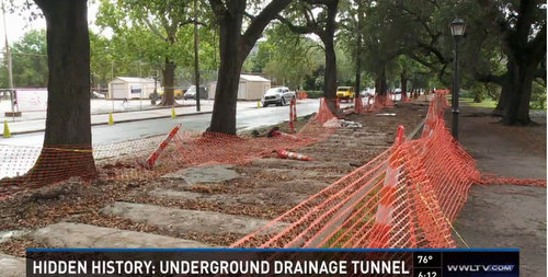 Construction netting surrounds the exposed drainage canal revealed under the Coliseum Square sidewalks in mid-May. (image via WWL-TV)