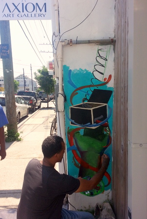 Bryan Brown paints a mural at the new Axiom Art Gallery on Freret Street in early June. (Robert Morris, UptownMessenger.com)