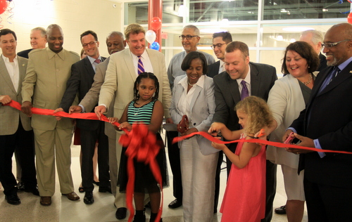 Audubon Charter School principal Janice Dupuy (center) -- flanked by two students and officials from the OPSB, the city, the state and federal governments -- cuts a ceremonial ribbon at Audubon Charter School's Broadway campus on Monday morning. (Robert Morris, UptownMessenger.com)