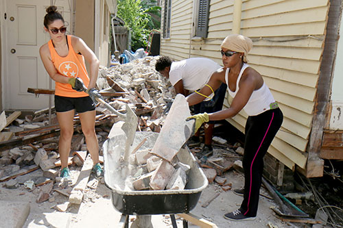 Brittney Furca, left, Lauren Cage, right, volunteers from LSU's Nursing School, and Devhante Woods, center, help clean up rubble after the house left the lot. (Zach Brien, UptownMessenger.com)