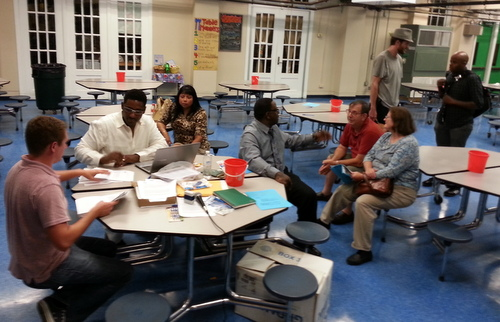 Matthew Brichetto and Stan Norwood (from left) count ballots while Alba Sanabria watches, and Glenis Scott speaks to Richard and Jane Dimitry at the end of the Freret Neighbors United meeting. (Robert Morris, UptownMessenger.com)