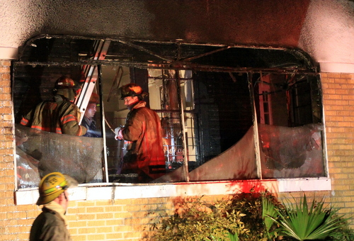 Firefighters look for hot spots in a house in the 2500 block of Palmer Street after a fire there early Friday morning. (Robert Morris, UptownMessenger.com)