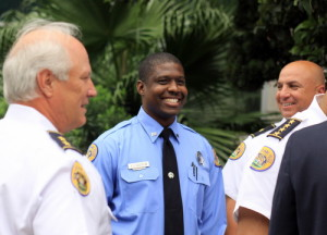 NOPD Officer Everette Route smiles as he's congratulated by Deputy Chief Bob Bardy (left) and Sixth District Commander Ronnie Stevens for his role stopping a robbery suspect Friday night. (Robert Morris, UptownMessenger.com)