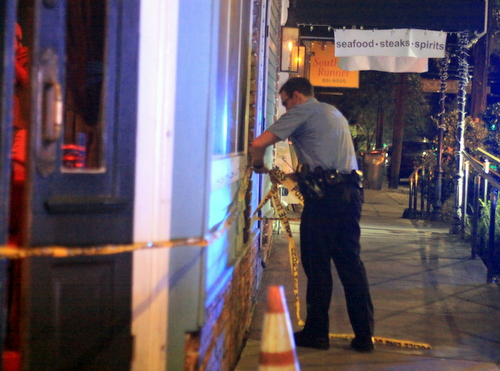 An officer runs crime-scene tape around the front door of Monkey Hill Bar on Magazine Street. (Robert Morris, UptownMessenger.com)