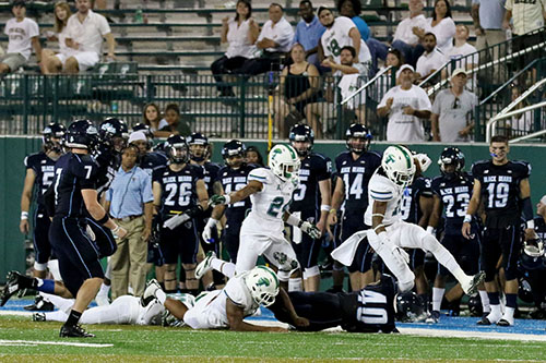 Tulane cornerback Dedrick Shy, right, runs out of bounds after intercepting Maine quarterback Dan Collins. Shy's interception was one of two Maine turnovers. (Zach Brien, UptownMessenger.com)