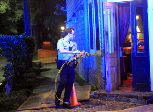A NOPD officer ties crime-scene tape on to the front door of Monkey Hill bar on Magazine Street after a robbery Monday night. (Robert Morris, UptownMessenger.com)