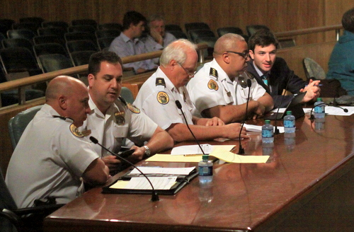 NOPD Commanders Ronnie Stevens and Paul Noel (from left), Deputy Chief Bob Bardy, Chief Michael Harrison, and spokesman Tyler Gamble confer prior to a hearing before the City Council on Friday. (Robert Morris, UptownMessenger.com)