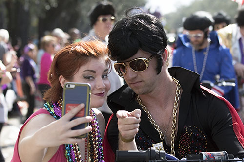 Alayna Dermid, left, takes a picture with a member of the Jailhouse Rockers in the Krewe of Carrollton. The Krewe of Carrollton was one of four parades that rolled uptown on Sunday. (Zach Brien, UptownMessenger.com)