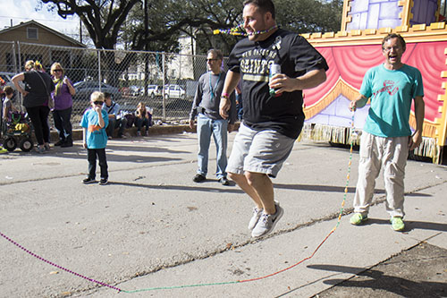 Jared Dubreuil, center, jumps rope with Jason Robertson, right, and his daughter Sophie, left, during a lull in the Krewe of King Arthur. King Arthur was one of four parades that rolled uptown on Sunday. (Zach Brien, UptownMessenger.com)