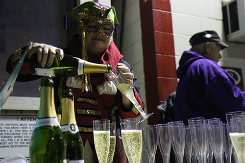 Sarah Hoffpauir pours glasses of champagne for the Phunny Phorty Phellows to welcome in Carnival season at the Willow Street streetcar barn. The event takes place on 12th night, 12 days after Christmas and is the first parade of Carnival season in New Orleans. (Zach Brien, UptownMessenger.com)