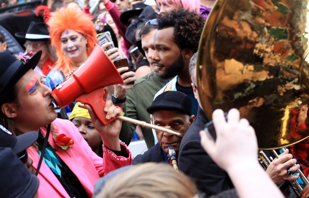 "Musician Win Butler of Arcade Fire sings ""Oh You Pretty Things"" into a megaphone on St. Peter Street in the French Quarter during Saturday's second-line tribute to David Bowie. (Robert Morris, UptownMessenger.com)"