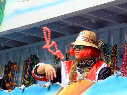 A rider throws beads as the Mystic Krewe of Femme Fatale rolled on St. Charles Avenue. (Robert Morris, UptownMessenger.com)