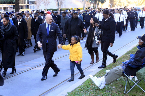 Mayor Mitch Landrieu confers with a young constituent as they march in the parade. (Robert Morris, UptownMessenger.com)
