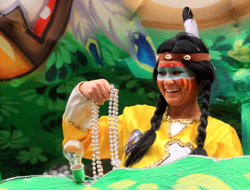 A rider laughs as she throws beads in the Krewe of Choctaw parade on Napoleon Avenue. (Robert Morris, UptownMessenger.com)