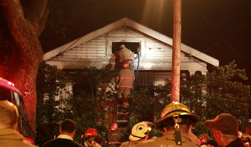Firefighters look for hotspots in the attic of 1019 Louisiana Avenue on Saturday morning. (Robert Morris, UptownMessenger.com)