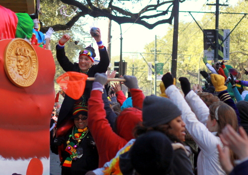 A parade goer celebrates receiving a coconut as the Krewe of Zulu rolls on St. Charles Avenue. (Robert Morris, UptownMessenger.com)