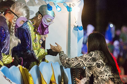 "A rider on the ""Bacchanahoppa"" float gives beads to an eager attendee. Bacchus 2016 rolled with the theme ""Flights of Delight."" (Zach Brien, UptownMessenger.com)"