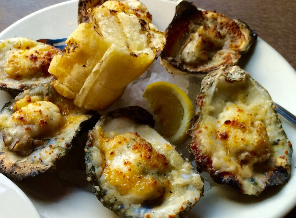 Charbroiled Oysters topped with Parmesan Pecorino Butter and Garlic Bread (Kristine Froeba)