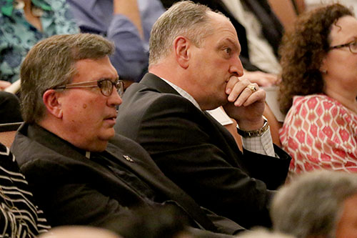 Rev. Kevin Wildes, S.J., Loyola University president, left, and Louisiana Gov. John Bel Edwards, right, listen to James Carville and Mary Matalin speak about the 2016 Presidential election in Rousell Hall. Carville, a Democrat, and Matalin, a Conservative, are two prominent speakers in their respective political circles. (Zach Brien, UptownMessenger.com)