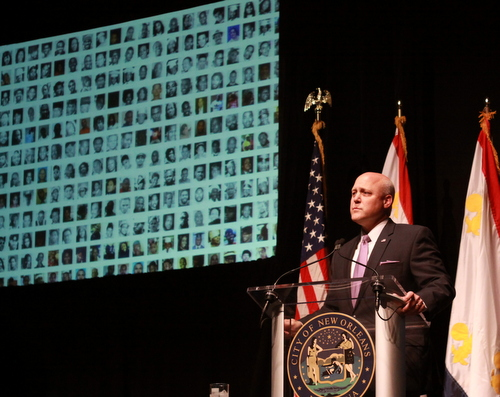 New Orleans Mayor Mitch Landrieu speaks at Tulane University while a projector screen displays the faces of victims of violence in the city. (Robert Morris, UptownMessenger.com)
