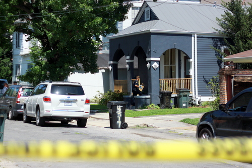 A crime-scene technician climbs the porch of a house in the 4300 block of LaSalle after a shooting there Thursday morning. (Robert Morris, UptownMessenger.com)