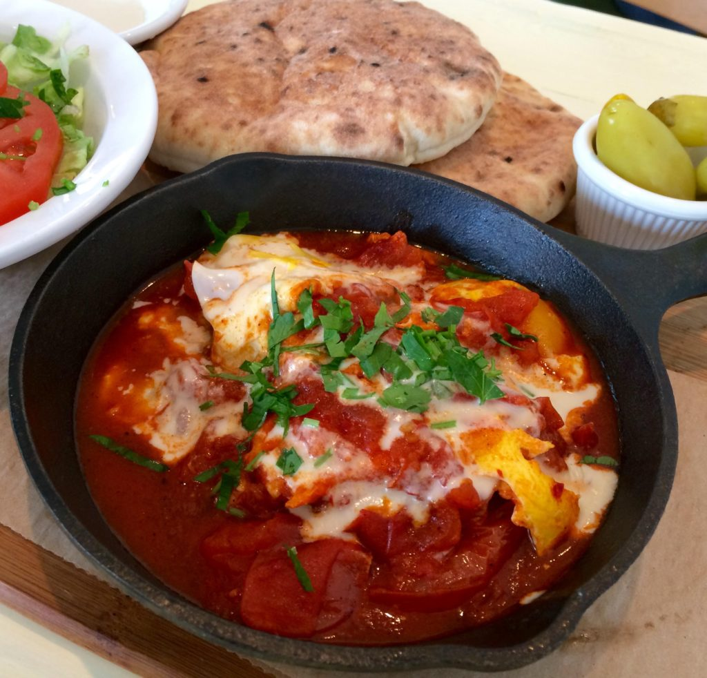 Shaksuka of Eggs Poached in Red Pepper and Tomato Sauce, with Tahini, Pita, and Salad. (Kristine Froeba)