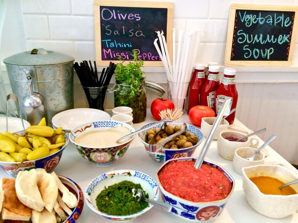 Tasting Bar of Amba, Schug, Shifka, Tahini, Olives, Fresh Salsa, and Spices. (Kristine Froeba)