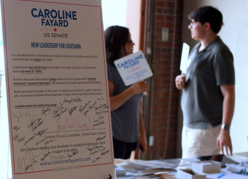 A placard at the rally displays Caroline Fayard's pledge to take only 65 percent of her salary until Congress passes a law improving women's wages. (Robert Morris, UptownMessenger.com)