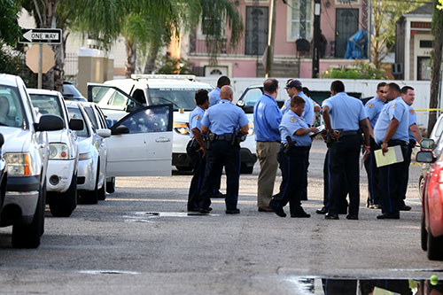 Police gather in front of a bullet-riddled car on Delachaise and South Robertson in Central City on Monday evening. The NOPD are investigating this fatal shooting. (Zach Brien, UptownMessenger.com)
