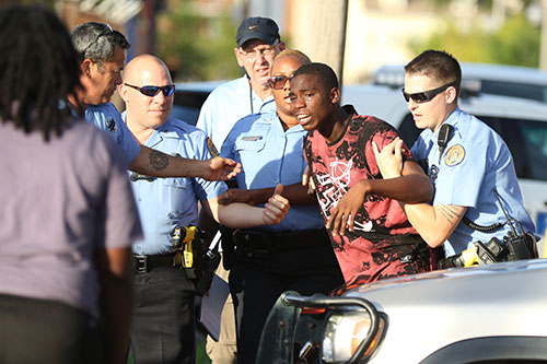 A visibly distraught man is pulled from the crime scene after rushing under the tape near the sight on a fatal shooting on Delachaise and South Robertson on Monday. The NOPD is currently investigating this shooting. (Zach Brien, UptownMessenger.com)