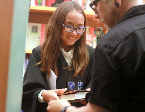 """Sisira Holbrook, first in line for the midnight release of """"Harry Potter and the Cursed Child,"""" smiles in anticipation as Octavia employee James Wilson hands her a copy of the book. (Robert Morris, UptownMessenger.com)"""