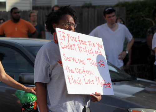 A protester holds a sign during a rally demanding justice for Eric Harris. (Robert Morris, UptownMessenger.com)