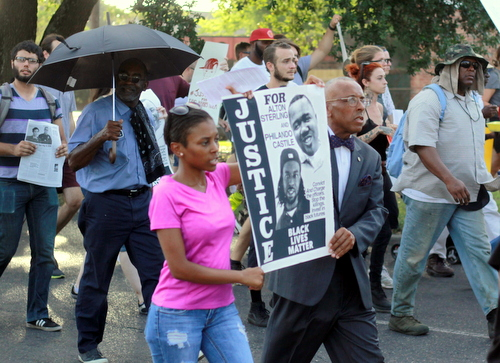 Protesters carry a sign as they march toward Lee Circle during a rally demanding justice for Eric Harris. (Robert Morris, UptownMessenger.com)
