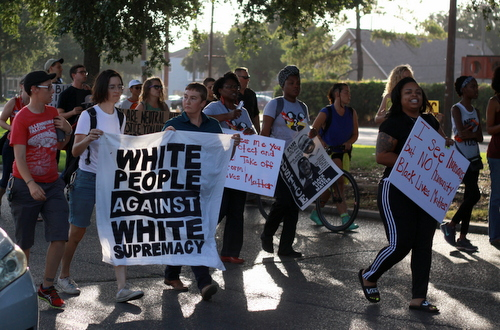 Protesters carry signs as they march toward Lee Circle during a rally demanding justice for Eric Harris. (Robert Morris, UptownMessenger.com)