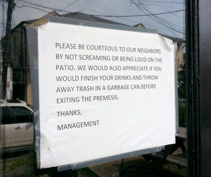 A sign in the front door of TJ Quills urges patrons to respect the neighborhood. (Robert Morris, UptownMessenger.com)
