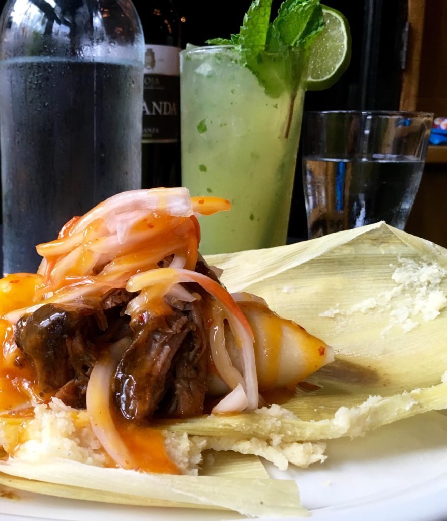 Tamal Criollo or Cuban Tamal of Sweet Corn and Roasted Pork topped with escaveche onions wrapped in corn husk; Classic Mojito (Kristine Froeba)